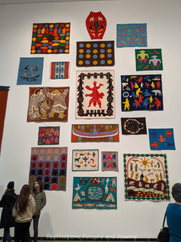 Collection of colourful Inuit woolen wall hangings with hand-stitched figures displayed on a two-story white wall at Qaumajuq