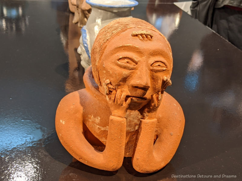 Clay sculpture of a woman's face resting  on her hands entitled Woman with Lice on Face by Donat Anawak