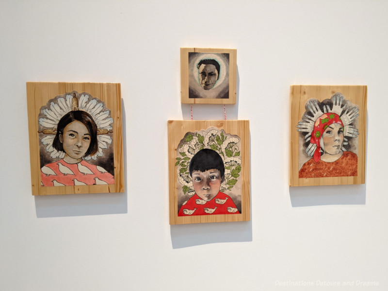 Four wood panel art pieces by Maya Sialuk painted with faces with halos of old Inuit culture items encircling their heads