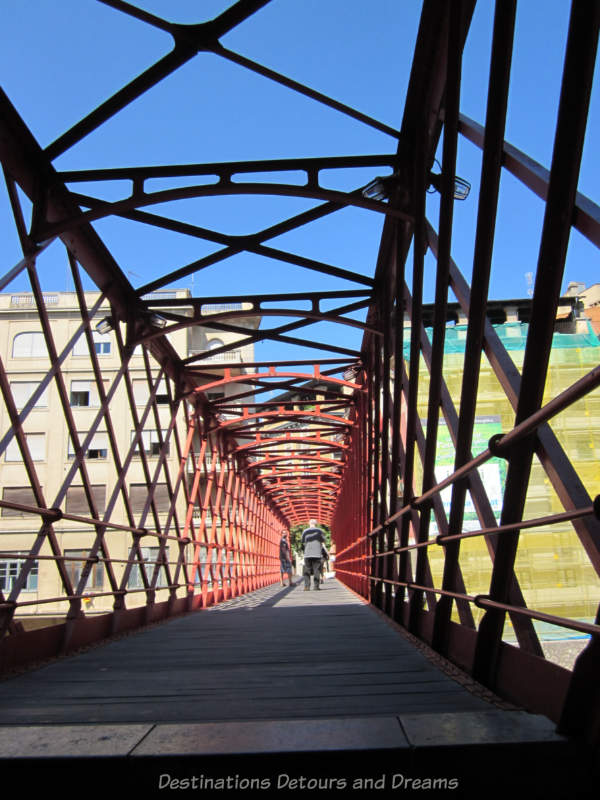 On the Eiffel Bridge in Girona, Spain, with crisscrossing bars forming side walls and a ceiling