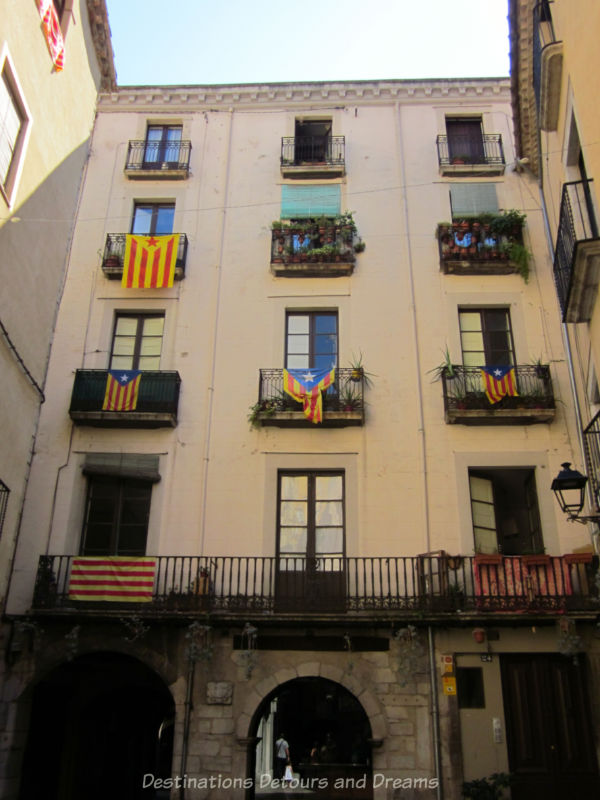 multi-story building with Catalonian flags draped over balcony iron railings
