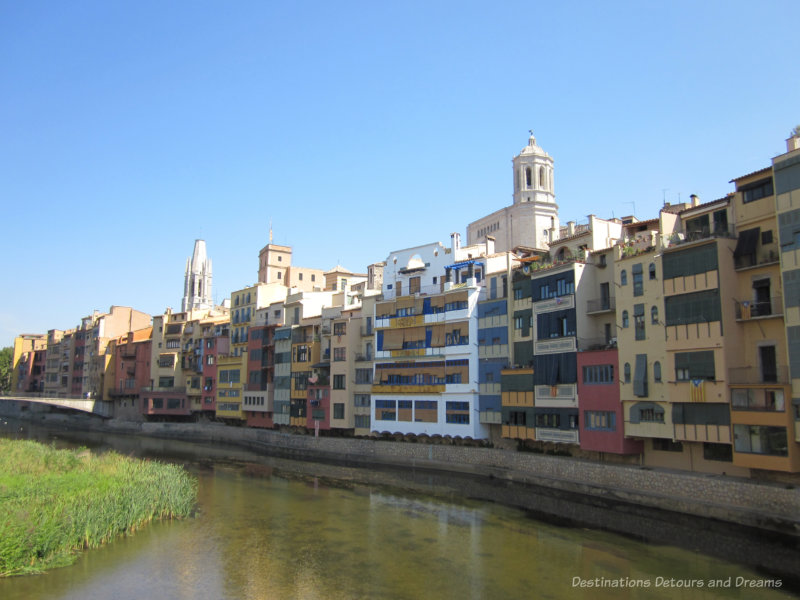 Four and five story row buildings painted in colourful colours lining the River Oynar in Girona