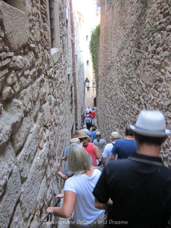 People walking down a steep narrow stone-walled stairway in Girona's old Jewish Quarter