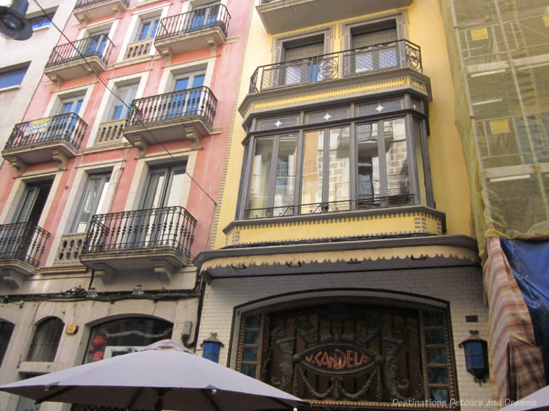 Pinkish and yellow exteriors of multi-story buildings with iron railed balconies in the Modernisme style in Girona