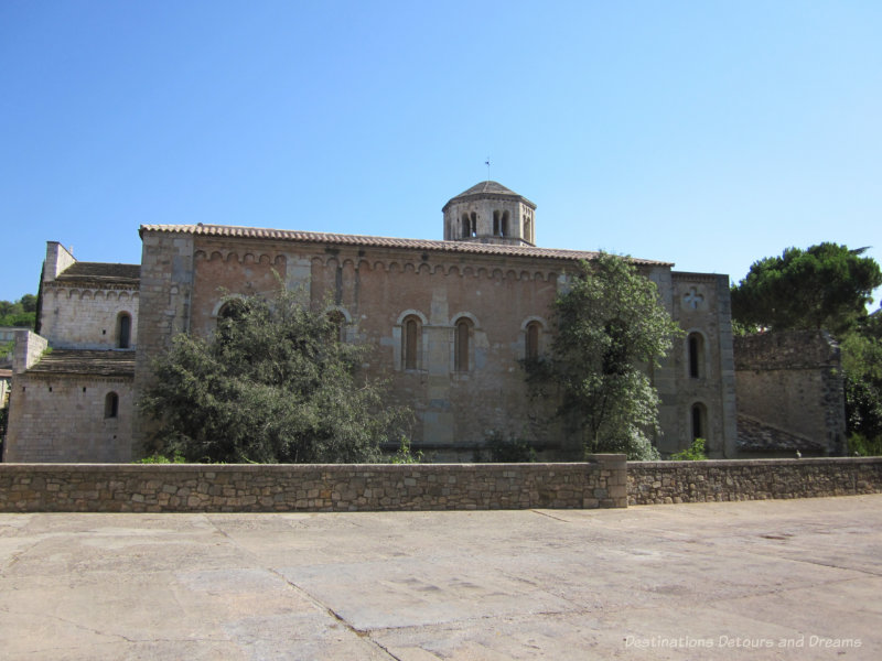 Stone Benedictine monastery building with an octagonal bell tower atop terra cotta roof in Girona