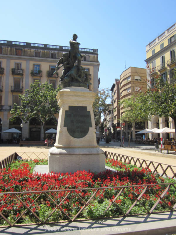 Statue of soldiers on a stone base surrounded by red flowers