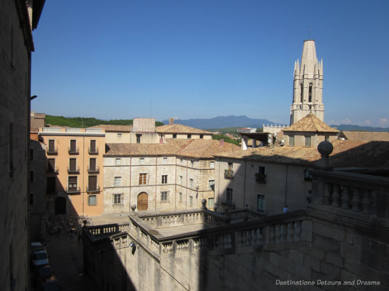 A view overlooking medieval stone buildings of Girona, Spain with hills in the background