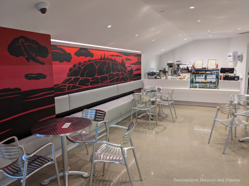 Café at Qaumajuq with food counter, chrome round tables and chairs, and a red and black Inuit art piece along one wallQau
