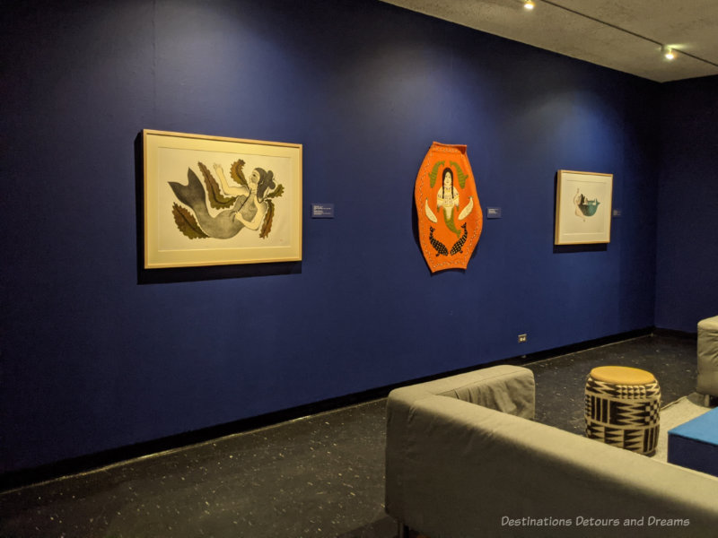 Art gallery space with dark blue walls displaying Inuit art work at the Winnipeg Art Gallery