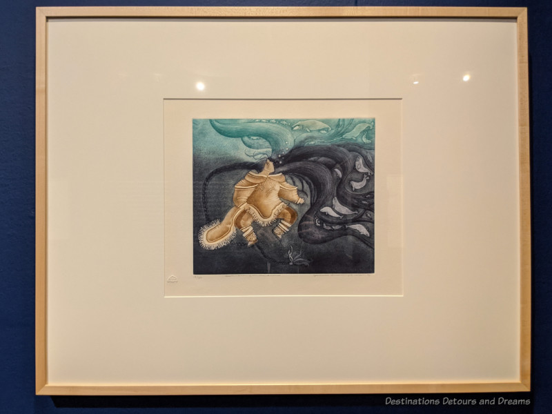 Painting of a figure in seal skin under swirls of black and teal water tells a story about the Inuit sea spirit