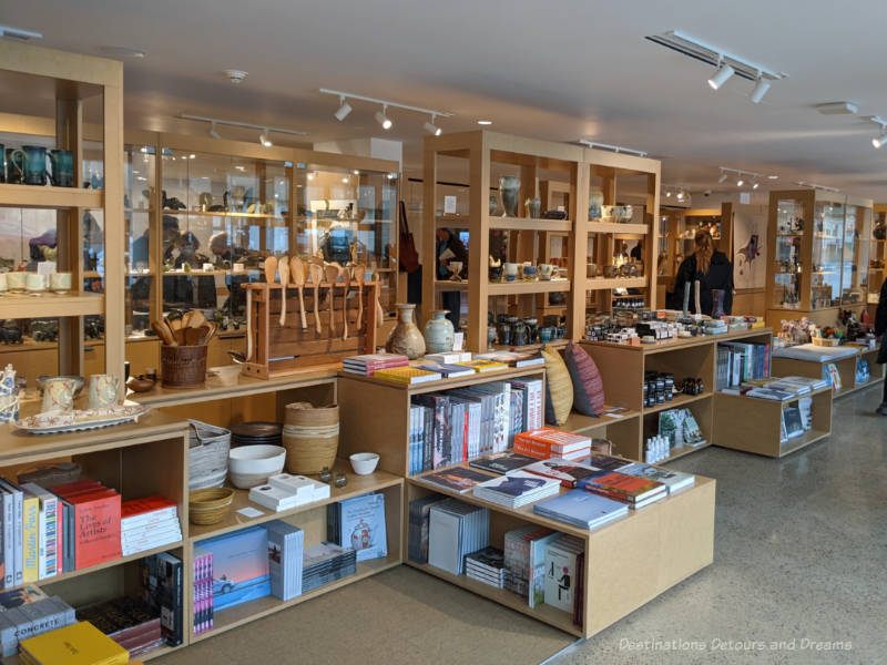 Row of shelves in WAG art gallery shop contain books, cushions, pottery, Inuit carvings, and other gift items