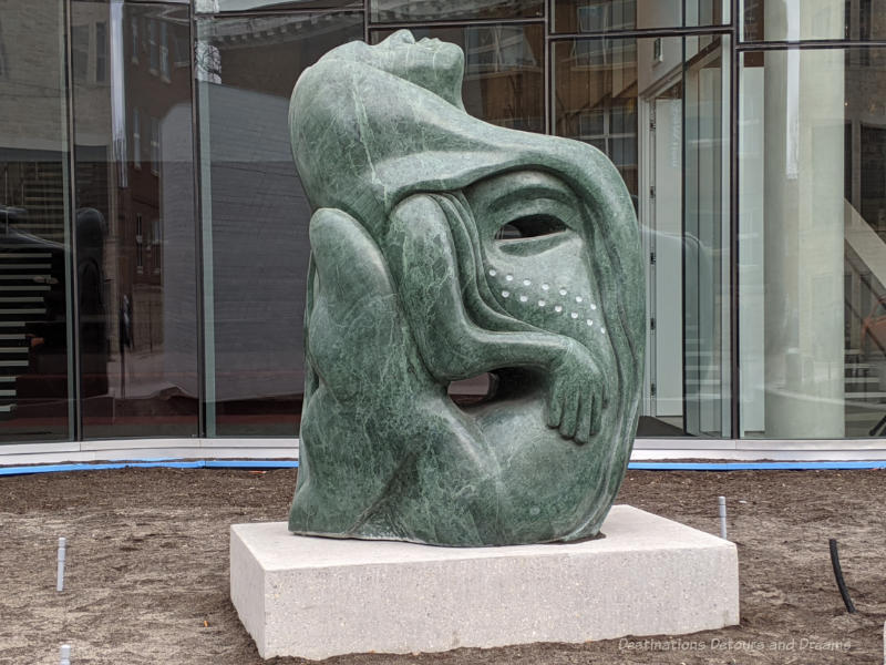 Green marble sculpture by Inuit artists Goota Ashoona is a sytlized version of Sedna, the Inuit sea spirit, and the tattooed face of a lady.