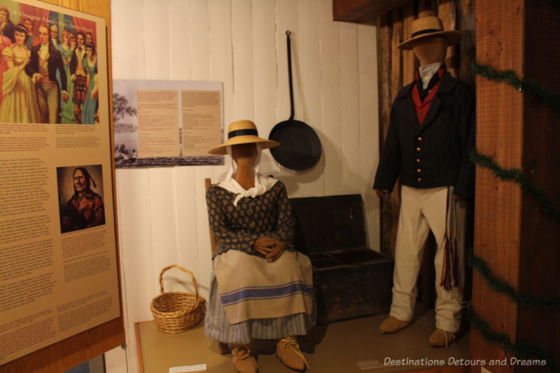 Museum display showing with panels of information and mannequins dressed as early French-Canadian settlers