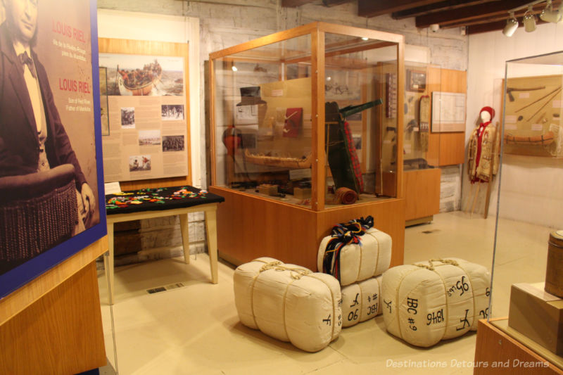 Room with displays (canoe models, clothing, packed parcels, written information) showcasing voyageur life and history at Saint Boniface Museum