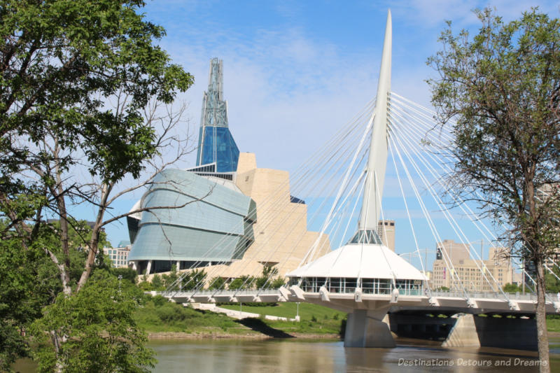 The granite wall, glass paneled wing, and tower of the Canadian Museum for Human Rights as view from across the river