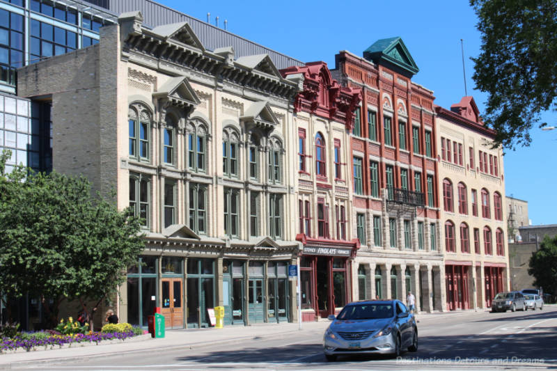 Facades of several early 20th century buildings on the front of a new build in Winnipeg's historic Exchange District.