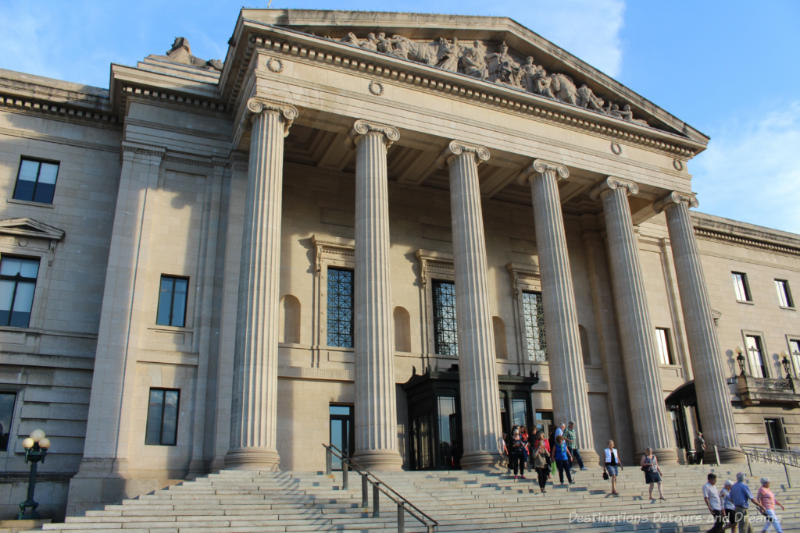 Front of the Beaux-Arts-Classical Manitoba Legislative Building with stone steps, six columns in front of the entrance, and allegorical carvings in the pediment