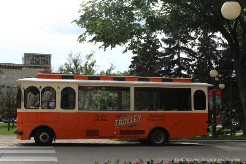 Orange and white trolley-style bus offering sightseeing tours of Winnipeg, Manitoba
