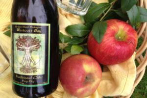 Bottle of cider beside two red apples. Photo courtesy of San Juan Islands Visitors Bureau.