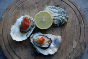 Three oysters on the shell with a half a lemon. Photo courtesy of San Juan Islands Visitors Bureau.