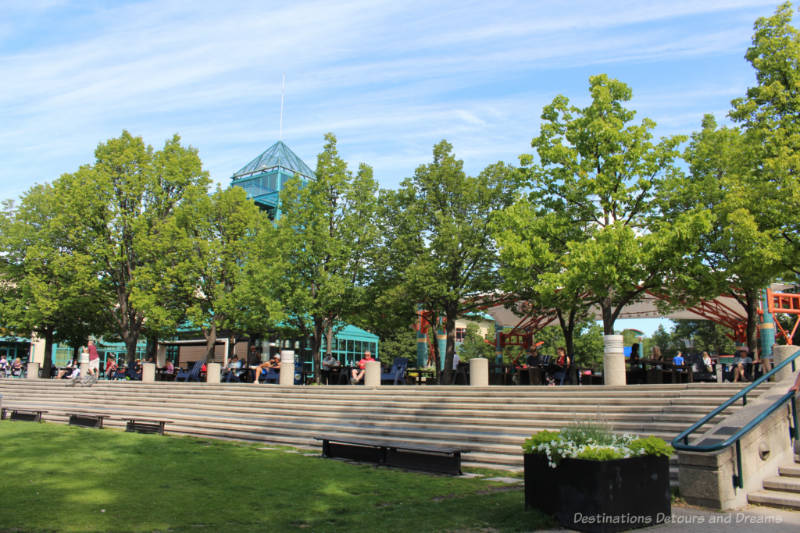 Grassy area in front of rows of stone steps/seating and upper level patio area at The Forks in Winnipeg, Manitops
