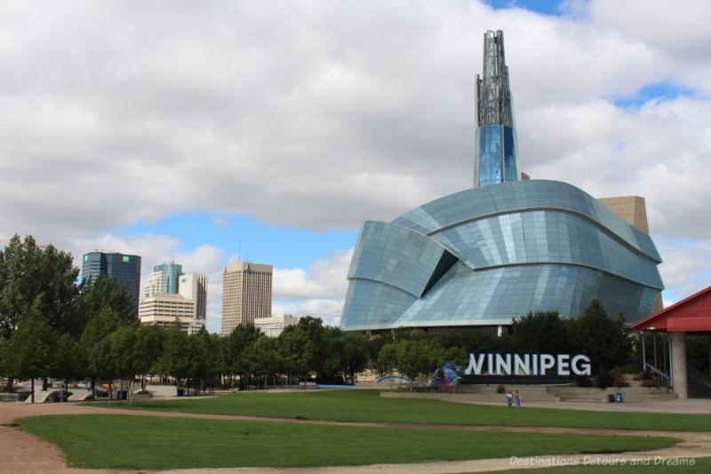 Winnipeg sign in front of the Canadian Museum for Human Rights Building and the Winnipeg skyline