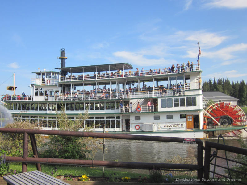 People inside and on the decks of a four-level sternwheeler cruising the river