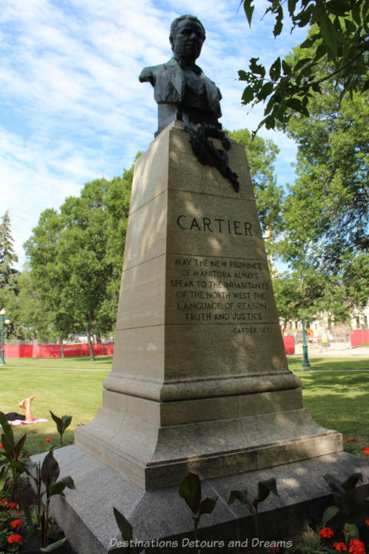 Bust of George Étienne Cartier atop a tall pedestal on the grounds of the Manitoba Legislative Building