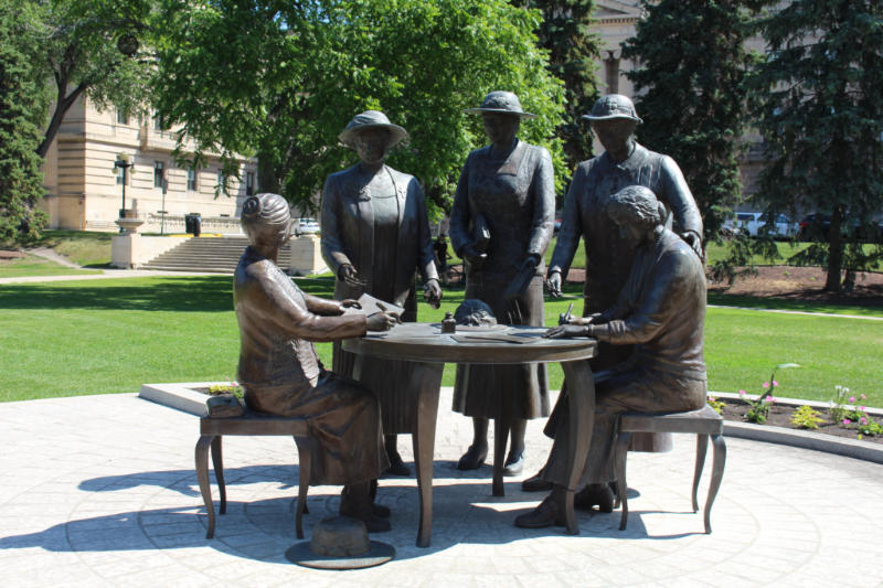 Statue of five women, two seated at a table and three standing representing the five women instrument in the Persons Case in Canada
