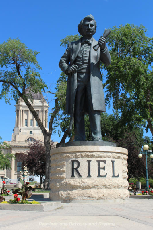 Full length statue of Louis Riel looking very statesmanlike on top a Tyndall stone base with the word RIEL on it.