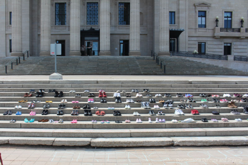 Pairs of shoes lined up on the stone steps of the Manitoba Legislative Building in memory of the children in unmarked graves on residential school sites