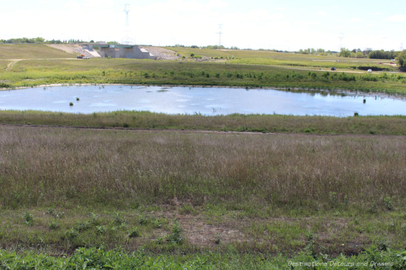A pond of water surrounded by prairie -  a channel left from Red River Floodway construction