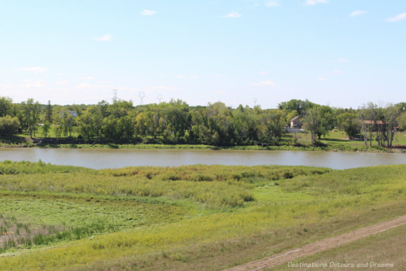 Calm, muddy river running through prairie with trees and houses on one side of the river