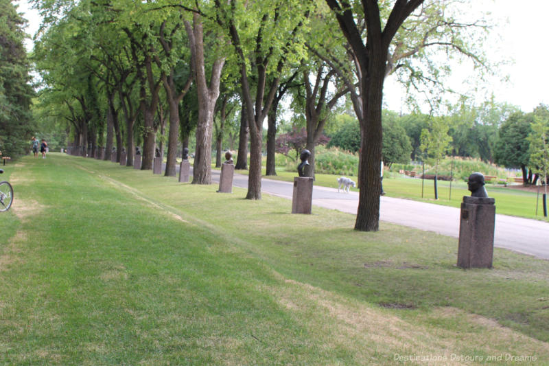 Green walkway between rows of mature trees with busts bordered by busts of important figures in a citizens hall of fame