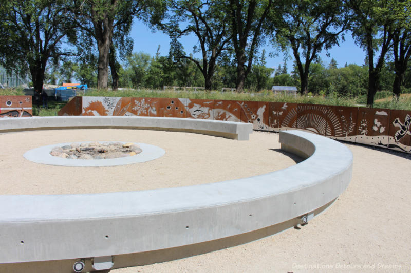 Circular cement seating around a fire pit in the Indigenous Peoples Garden at The Leaf in Winnipeg, Manitoba