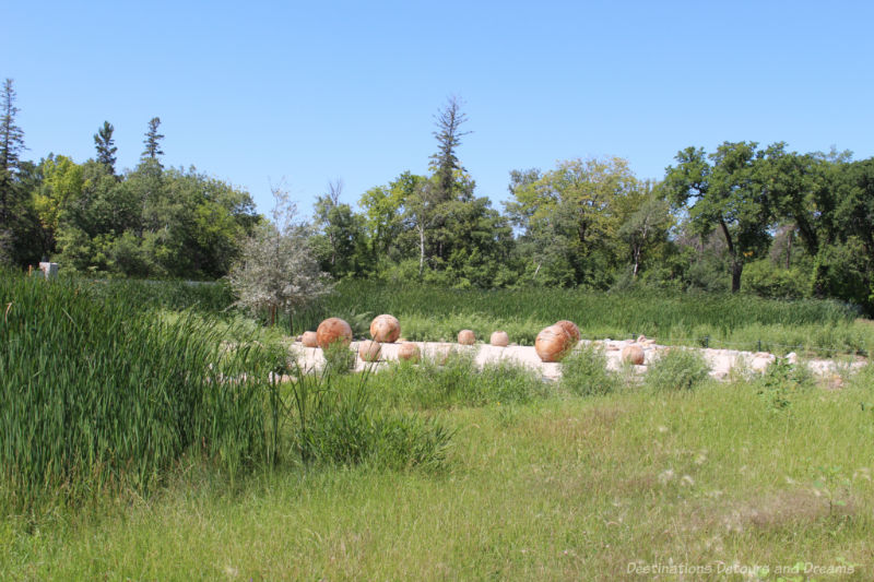 Carved wooden balls sit around a gravel circle amid a landscape of native grasses and shrubs
