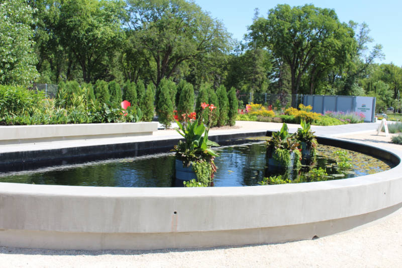 Cement half-circle shaped lily pond with path around it and gardens in the background