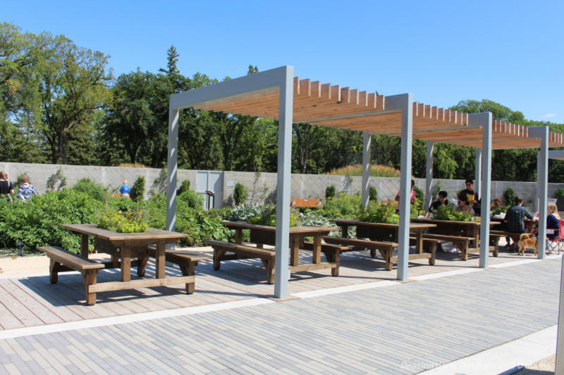 Several picnic tables under a pergola at the Kitchen Garden at Gardens At The Leaf in Winnipeg