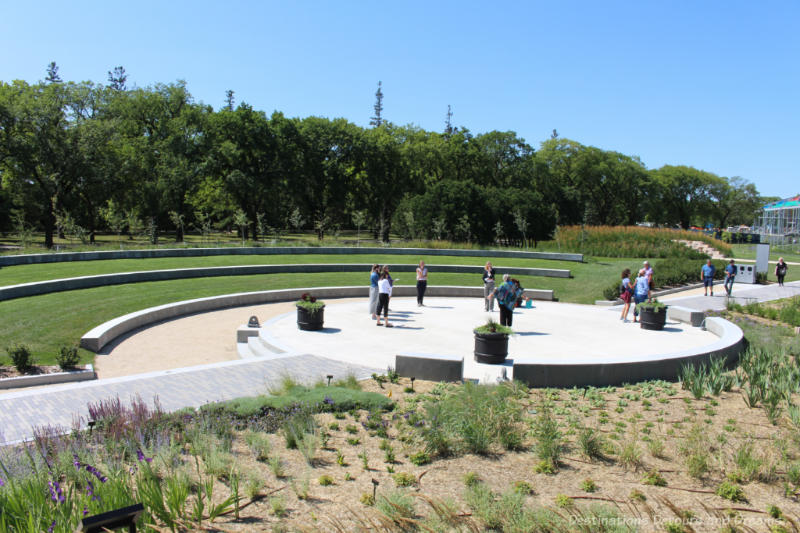 A cement stage in the centre of the Gardens at the Leaf in Winnipeg, Manitoba with gentle tiered seating on the lawn in front of it