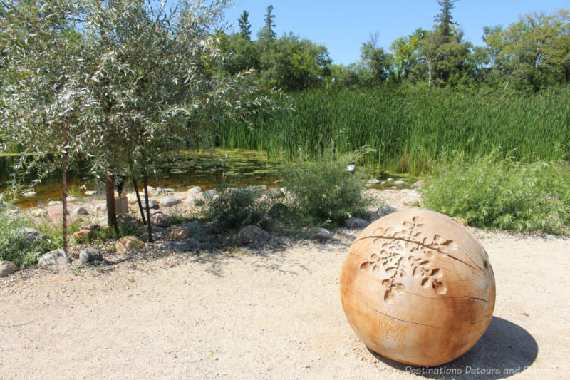 Large carved wooden ball on gravelled are in front of pond surrounded by tall grasses and shrubs
