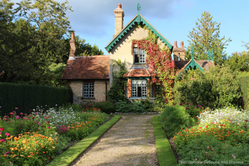 Gravelled pathway lined with massed of blooming flowers leading to a gingerbread house style stone cottage