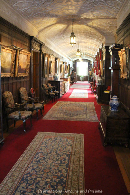 Long hallway with red carpeting covered with Persian rugs and art work hung along its wood panel walls
