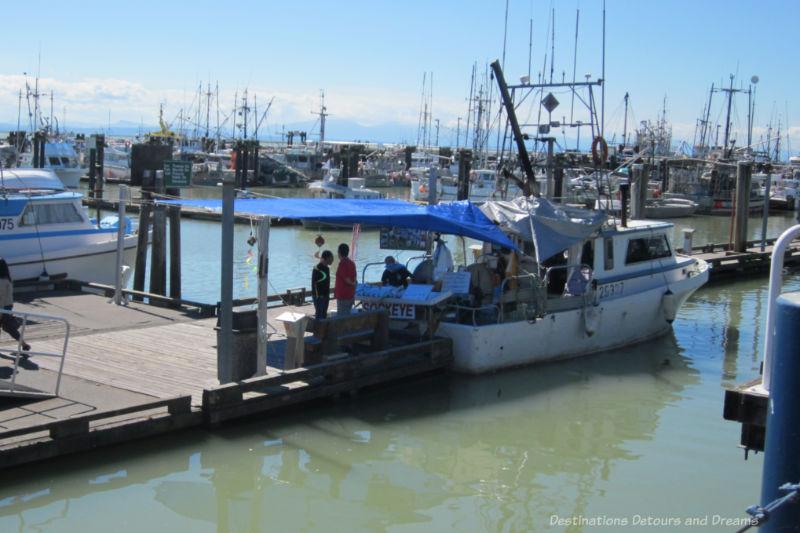 Fishing boat docked at boardwalk selling fresh fish in Steveston, British Columbia