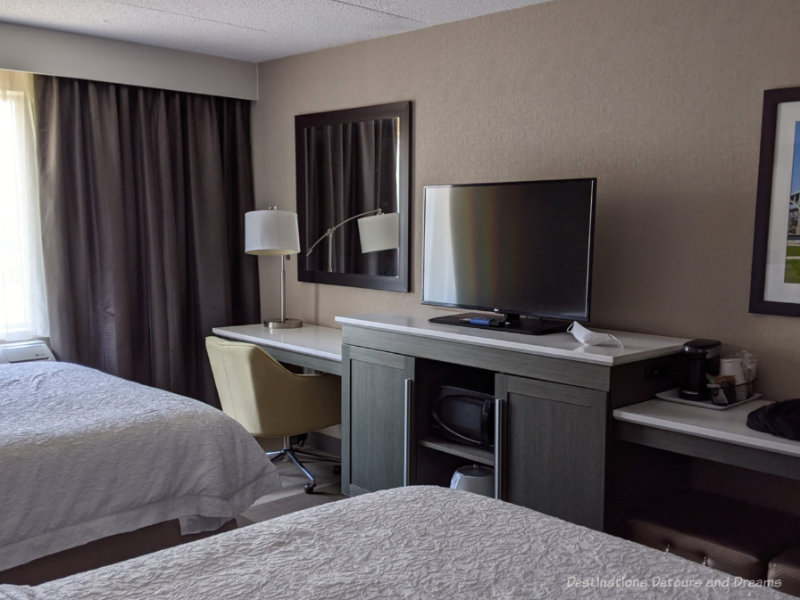Hotel room showing two beds, desk, and TV stand