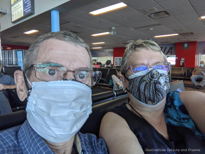 Man and woman wearing face masks inside airport terminal