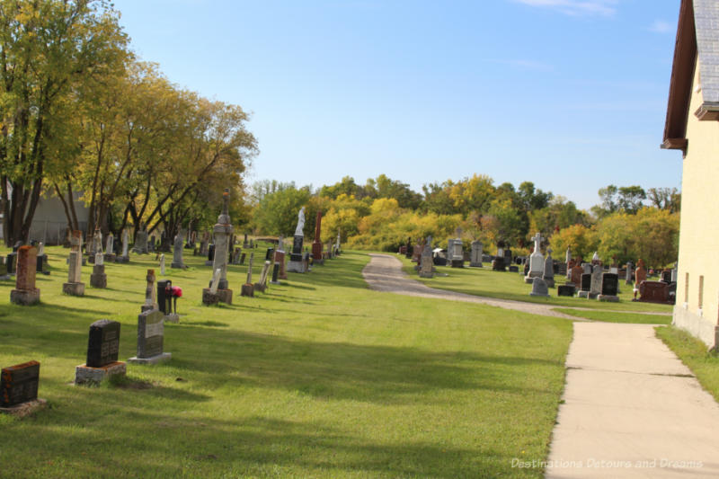 Cemetery on church grounds with trees turning fall colours in the backgroun