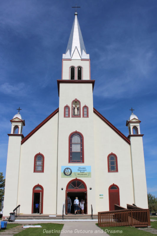 White former church with reddish trim, centre steeple, and side spires