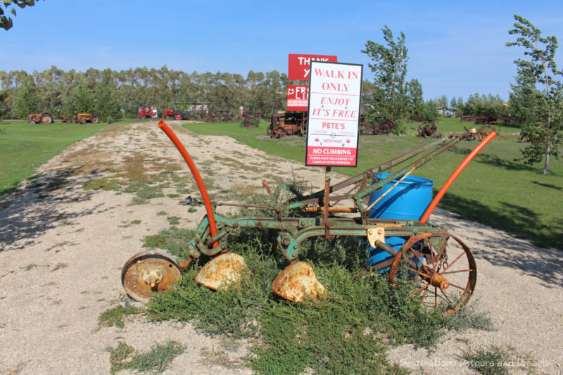Rusted piece of machinery with sign saying Pete's leads to a field containing a collection of old machinery