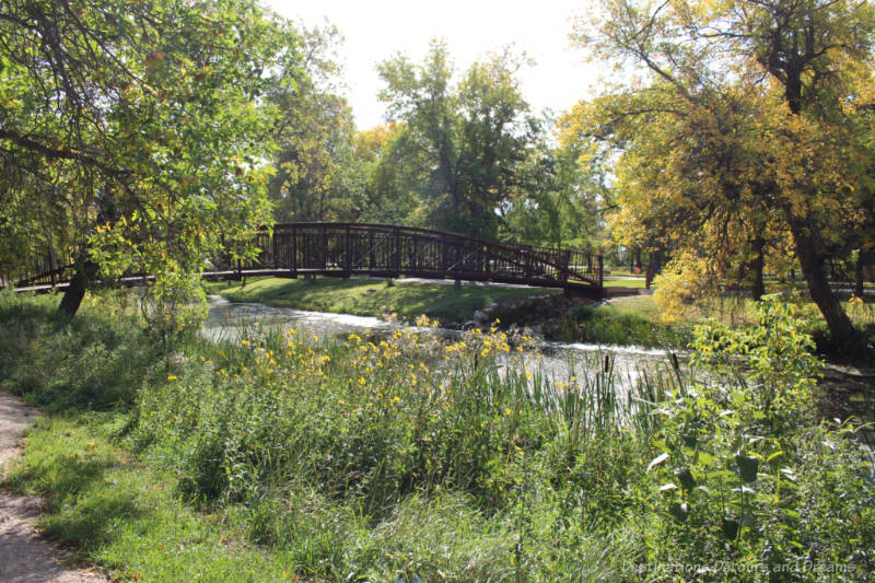 Brown foot bridge crossing a small river into a grassy treed park