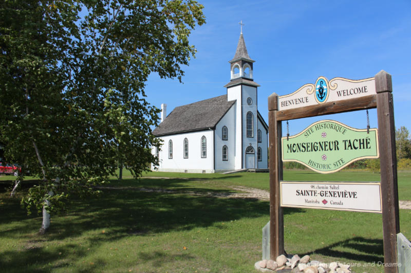 White wooden church with front steeple and sign indicating it is the Monseigneur Tache Historic Site
